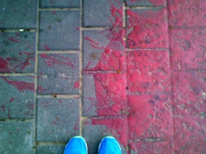 Red paint spill on pavement